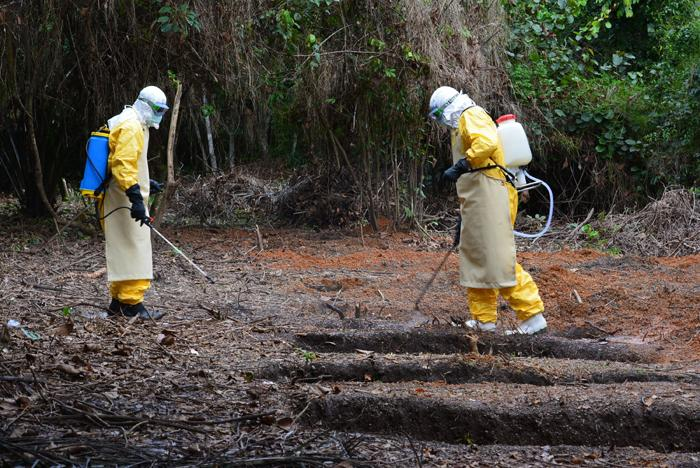 The burial team at the International Medical Corps Ebola treatment unit in Liberia's Bong County sprays the grave of 11-year-old Anna Singbeh with a chlorine disinfectant.  (Robyn Dixon/Los Angeles Times/MCT)