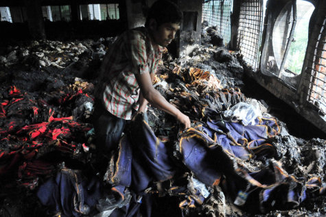 A worker inspects a burnt garment after a fire broke out at a garment factory building in Dhaka, Bangladesh, May 9, 2013. Shortly before midnight Wednesday, a fire swept through a garment factory in the capital Dhaka, killing eight people, including its managing director and a top police official. Initial reports suggested the fire in the 11-story building was caused by a short circuit on the second floor, which spread to the third and fourth floor where the factory was located.(Shariful Islam/Xinhua/Zuma Press/MCT)