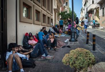 Syrians sit on a sidewalk where they have been sleeping in Izmir, Turkey, while they wait to attempt reaching Greece by boat on Sept. 3, 2015. This year, some 220,000 war refugees and economic migrants have arrived in Greece from Turkey and other Mediterranean jumping off points, according to U.N. figures. (Alice Martins/McClatchy/TNS)