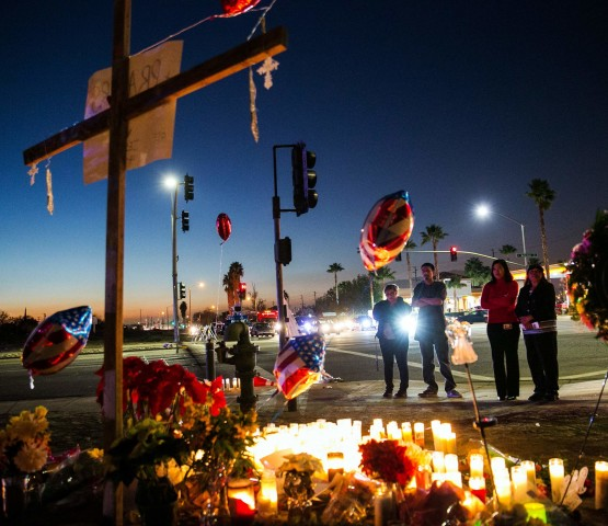 People stream in steadily throughout the day to pay their respects at the memorial site for victims of Wednesday's mass shootings near the Inland Regional Center in San Bernardino, Calif., on Friday, Dec. 4, 2015. (Marcus Yam/Los Angeles Times/TNS)