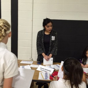"""Class of '14 graduate and current college sophomore, Monica Herrera, speaks to middle schoolers about the university she attends, John Hopkins. The small gym was set up similar to the college fair, only this time there were alumnae spoke on behalf of the college they attend. """"The first semester I didn't join any clubs or extracurriculars, and it was hard. The second semester I did and it was better,"""" Herrera said. Photo courtesy of Sharon Roy."""