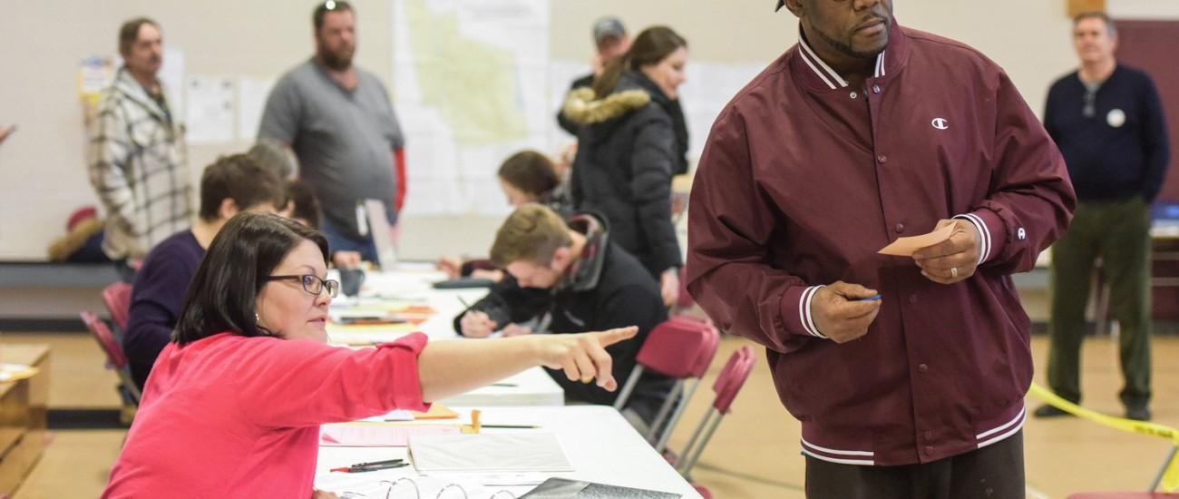 A New Hampshire voter checks in at a polling station in Manchester, N.H., on Tuesday, Feb. 9, 2016, as both Republicans and Democrats register votes in their respective presidential primaries. (Bao Dandan/Xinhua/Sipa USA/TNS)