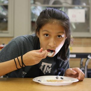 Anika Villavicencio (7) eats a pancake made at ARS Pancake Art Breakfast and Art Supply Swap. Her mom volunteered at the event and made gluten free pancakes for those with dietary restrictions.
