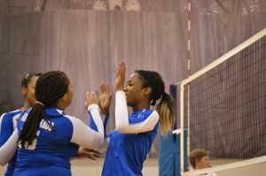 JV player Alexis Taylor high fives her teammates after a awesome play