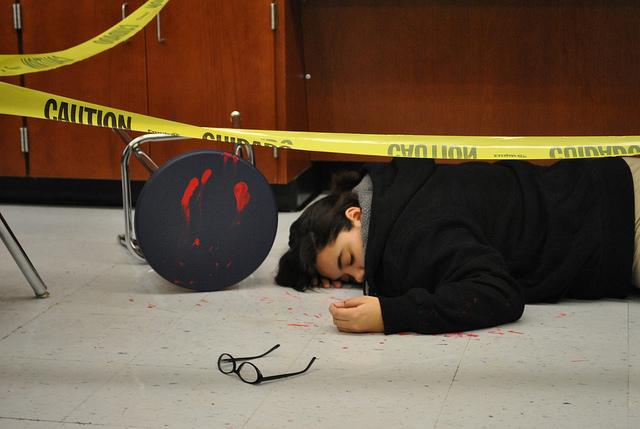 Angelique acts like a dead person at a crime scene for the biomedical pathway showcase
