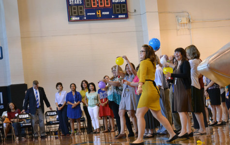 The science teachers throw balloons out to the crowd, led by Ms. Sauter. Teachers were introduced by their subject area  in the Monday assembly.