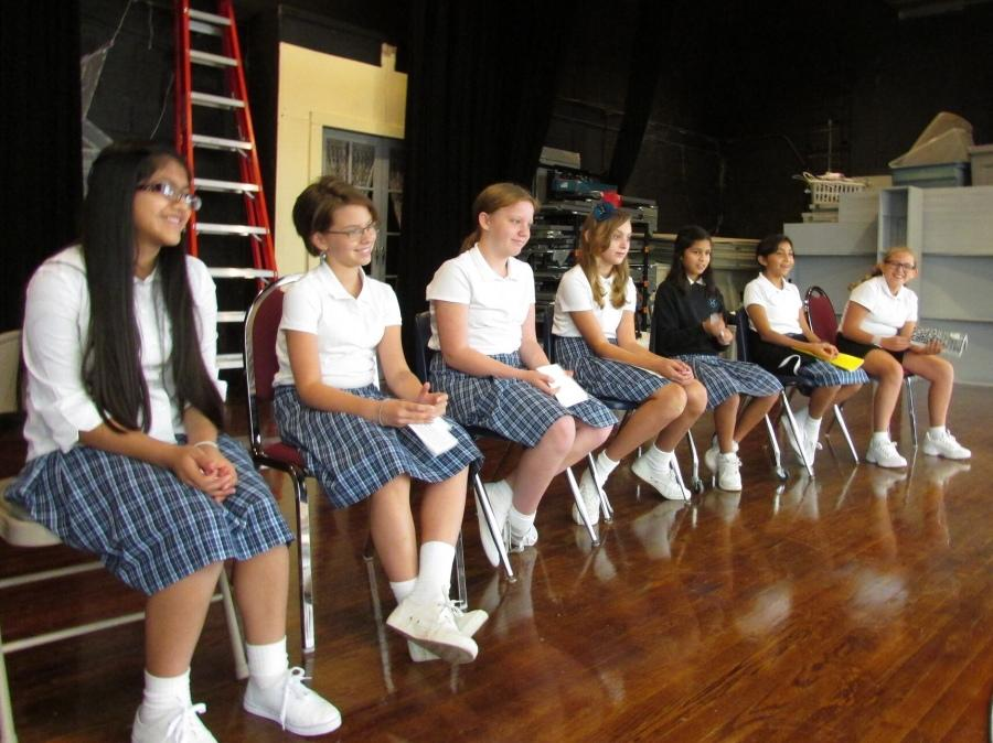 The girls sit in a row and are called up one-by-one to present their speech. They have practiced for the past week: in front of friends, family and mirrors. (left to right: Marlin Gomez, Emma Tatum, Arden Price, Saskia Solotko, Alex Sanmiguel, Alexa Perez, Calyssa Marquez)