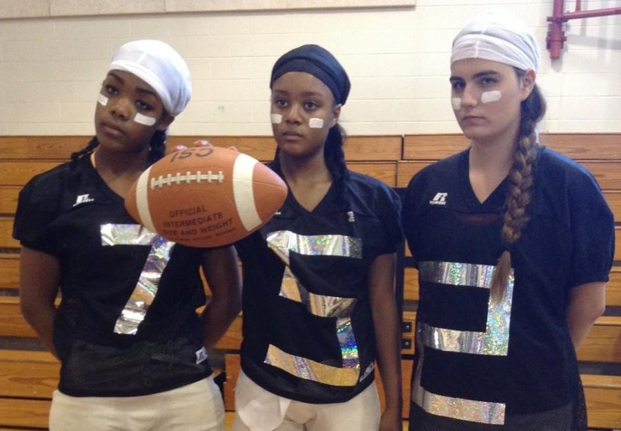 Alexis Taylor, Jada Washington and Eliza Martin dress up as football players to get pumped for the game. This is the 3rd year the team undertook the idea of team costumes.