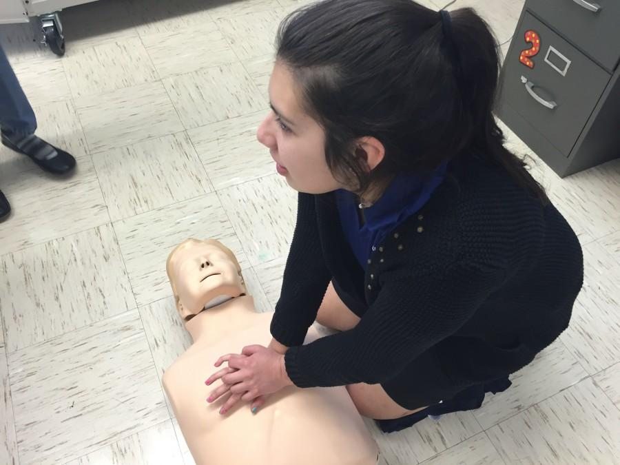 Bio-medical student Andrea Cazares practices her compressions on a CPR dummy. Students must master the steps of CPR to receive certification.
