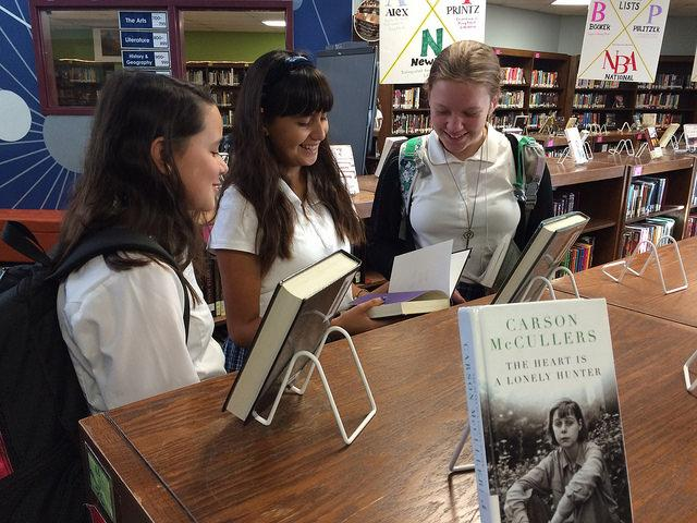 Friends Frida Capitan, Anabelle Glass, and Arden Price (7) look at books in the library before school starts. Anabelle will also be attending the festival on Saturday, after being convinced by Frida to attend.