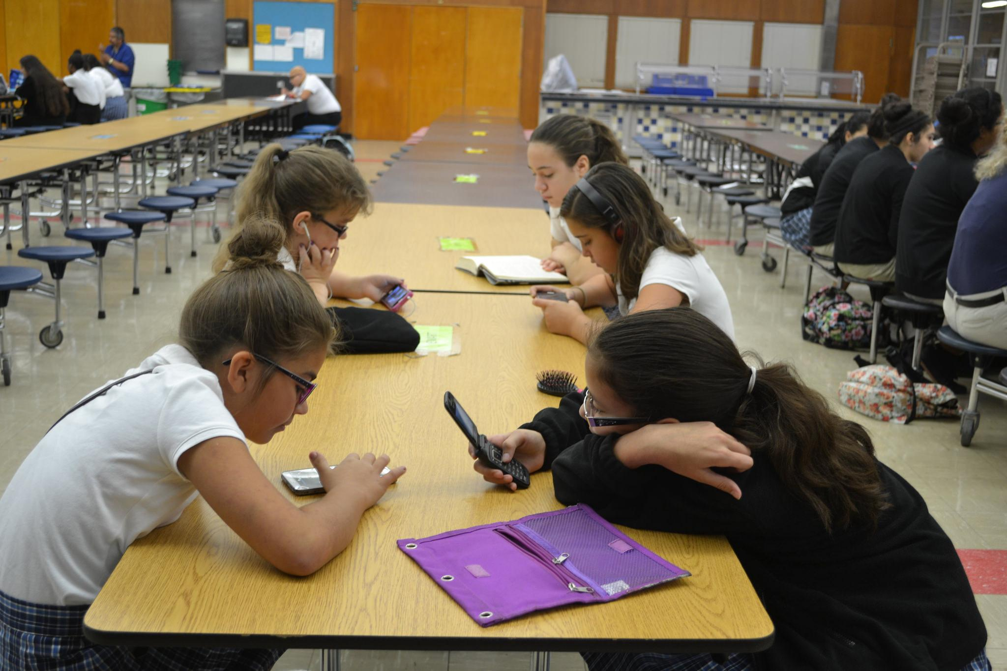 Middle schoolers use their phones before morning assembly. Photo by Mayrin Silva