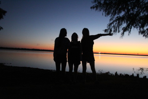 Seniors Rewon Shimray, Katya Witliff and Georgia Oldham  pose in front of the sunset at their last high school cross country meet.
