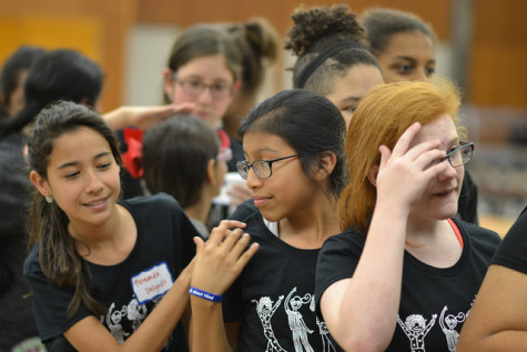 Fernanda Delgado (6) and Adriana Martinez (6) wait in line for dinner at the 2015 YWPN Sisterhood Sleepover behind guests from the San Antonio girls school.