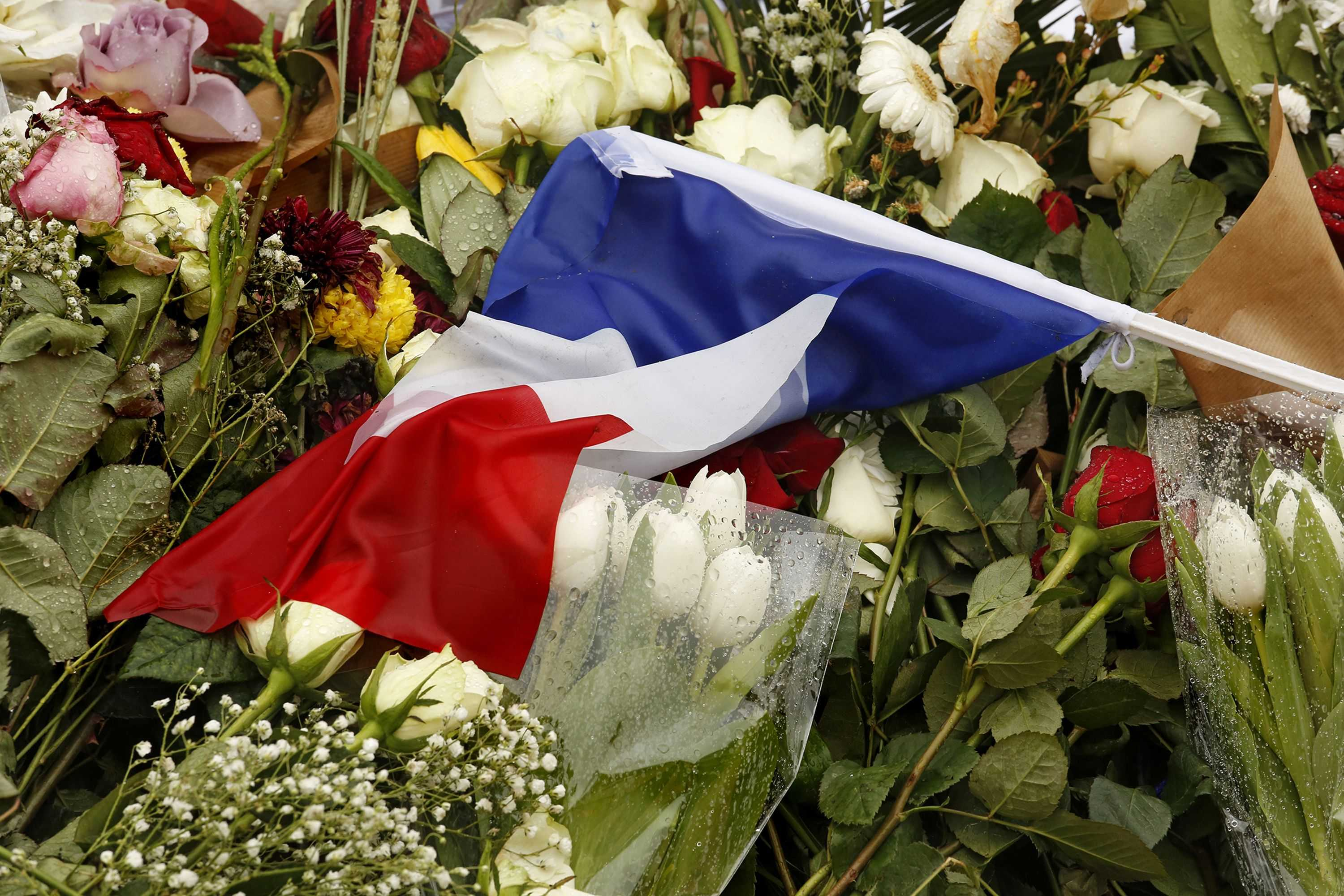 Light rain falls on memorial cards, flowers and candles in Paris on Thursday, Nov. 19, 2015. (Carolyn Cole/Los Angeles Times/TNS)