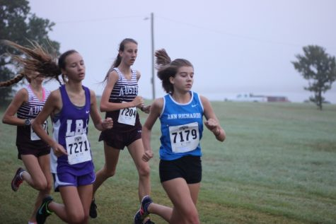 Olivia Rose (10), varsity cross country runner, races barely ahead of her fellow competitors. Photo by Madeline Schell.
