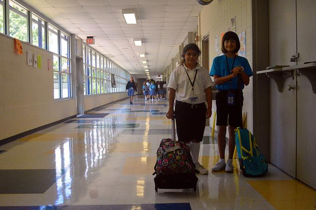 Hannah Olson (6) and Claire Moore (6) stand with their rolly backpacks in an empty hallway.  Photo taken by Alejandra Wait.