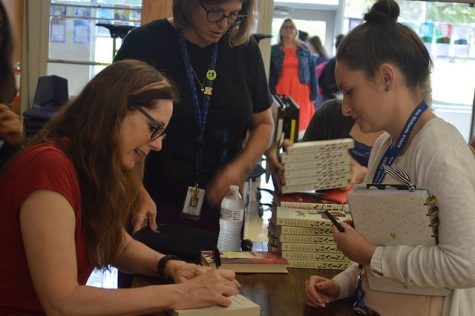 "High school counselor Amy Bryant gets her copy of ""Chains"" signed by Anderson. Many students and faculty brought their copies of Anderson's books to be signed after the presentation."