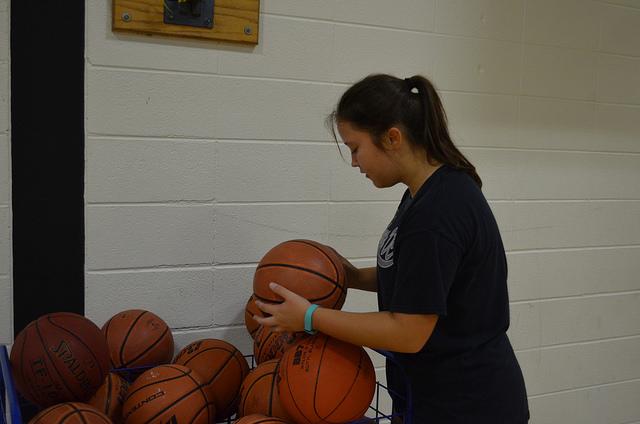 Ginger Rodriguez (10) pick up a ball from the pile during basketball practice. They were practicing various drills in the small gym.