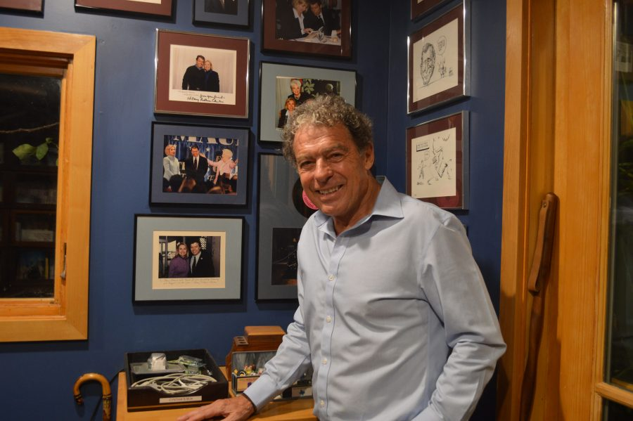 Gary Mauro stands in front of his wall filled with photos of him, Hillary Clinton, and Ann Richards. Over the years of working as a Texas politician, he has worked closely with both of them. Photo by Ally Wait.