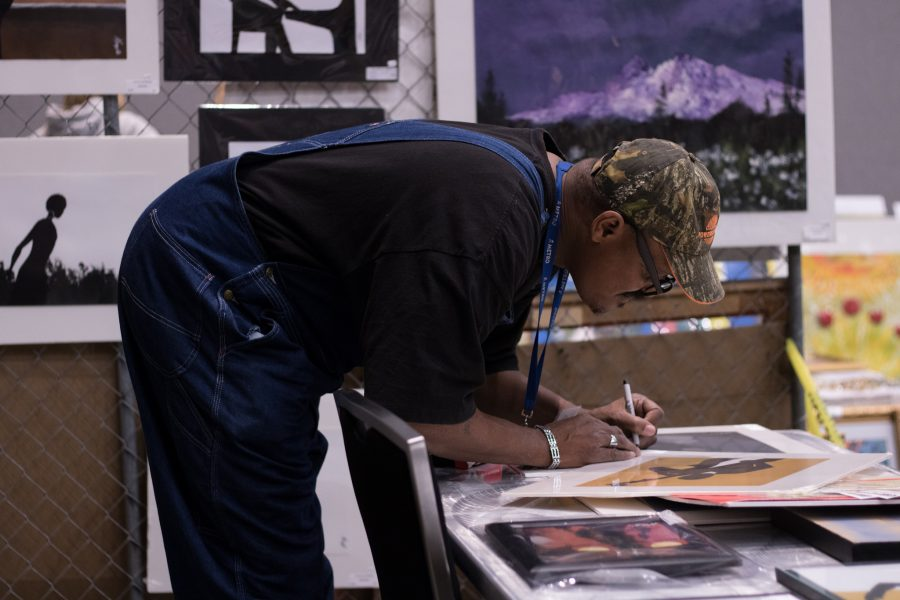 Hugh Miles works on his art at the Art from the Streets show and sale.