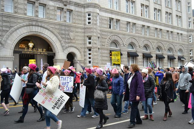 Marchers+pass+the+Trump+International+Hotel+on+12th+street.+A+chorus+of+shame+went+through+the+crowds+as+they+moved+passed.+The+original+march+route+didnt+encounter+Trump+hotel%2C+however+the+planned+route+couldnt+handle+the+number+of+people%2C+so+nearby+streets+we+flooded+as+well.+Photo+by+Gus+Flores.