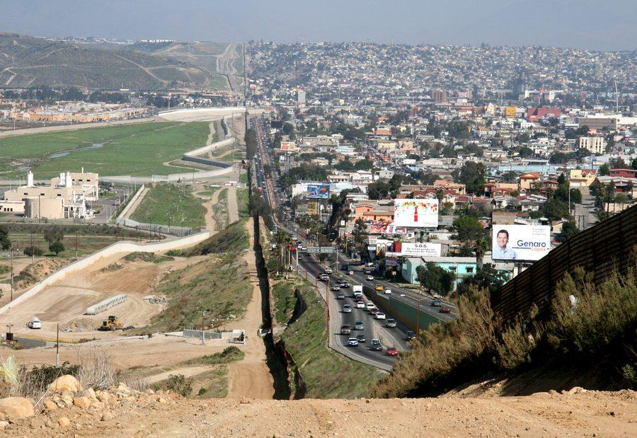 A small fence separates densely populated Tijuana, Mexico, right, from the United States in the Border Patrol's San Diego Sector.  Construction is underway to extend a secondary fence over the top of this hill and eventually to the Pacific Ocean.