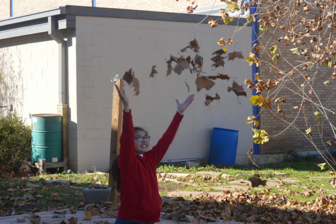 "Arianna Rodriguez (6) throws leaves in the Ann Richard School courtyard on January 3. Rodriguez was modeling for intersession photojournalists who practicing action shots. ""I love nature and how the sun shines,"" Rodriguez said.  Photo by Briana Mondragon (6)."