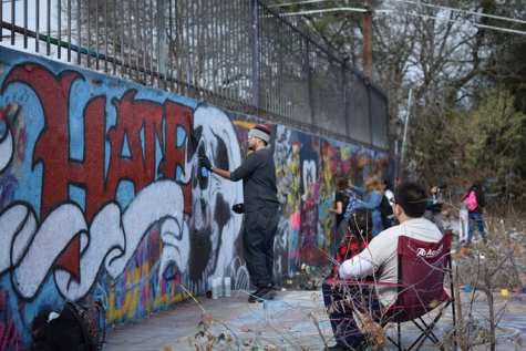 A graffiti artist finishes up his art on January 4th, 2018 at the Austin Graffiti Park, atop Castle Hill. A few watchers observe him spray paint. Since the art is recent, you could go up to The Graffiti Park and see it for yourself, right at the very top and very center of the hill. Photo by Nina Drutz
